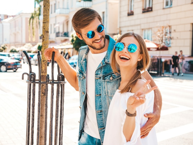 Smiling beautiful girl and her handsome boyfriend posing in the street. Free Photo
