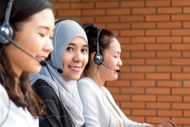 Smiling beautiful muslim woman working in call center Premium Photo