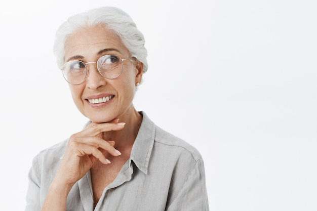 Улыбающаяся красивая старшая женщина в очках смотрит мечтательно в правом верхнем углу Бесплатные Фотографии