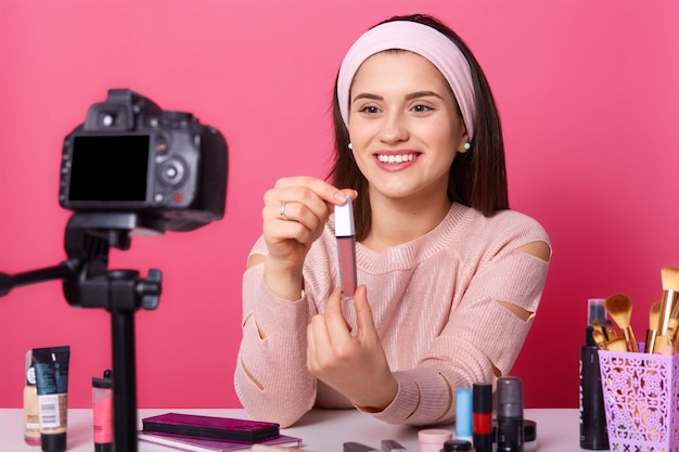 Smiling beautiful vlogger showing her new lipstick to subscribers, looks happy, holding it in both hands, posing isolated over pink wall in studio, demonstrating new cosmetic products. Premium Photo
