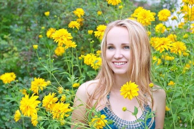Smiling beautiful woman among  flowers Premium Photo