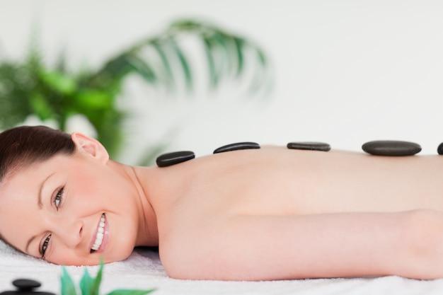Smiling beautiful woman having a stone massage Premium Photo