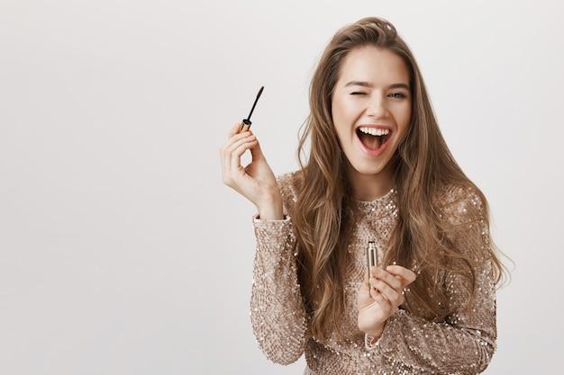 Bella donna sorridente che usando mascara Foto Gratuite