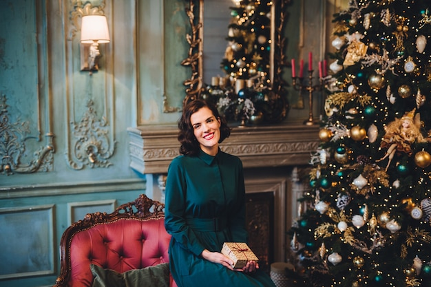 Smiling beautiful woman wears nice dress, sits near christmas tree in room, holds present Premium Photo