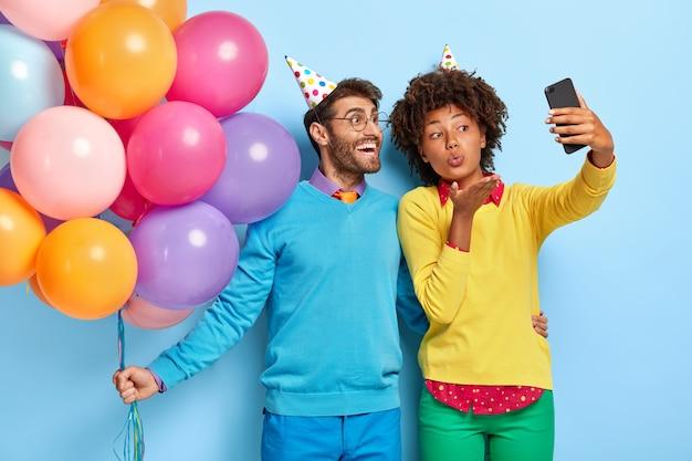 Улыбаясь красивая молодая пара на вечеринке позирует с воздушными шарами Бесплатные Фотографии