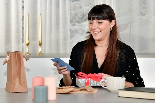 焦点が合っていない背景に青い封筒と銀で包まれたギフトボックスを保持している美しい若い女性の笑顔。 無料写真