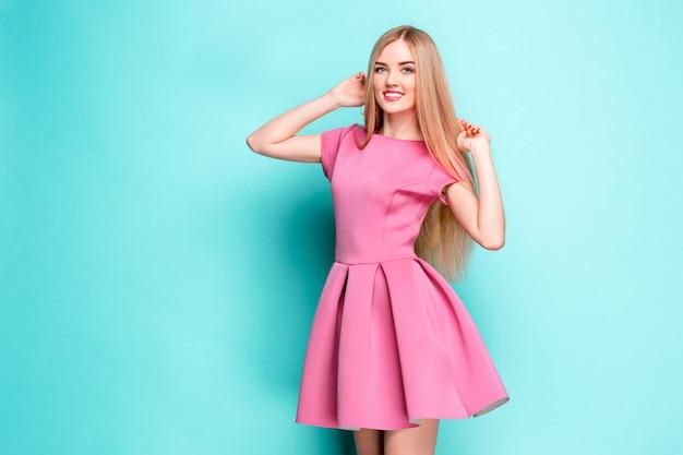 スタジオでポーズピンクのミニのドレスで美しい若い女性を笑顔 無料写真