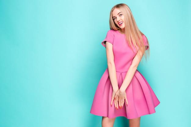 Улыбка красивая молодая женщина в розовом мини-платье позирует Бесплатные Фотографии