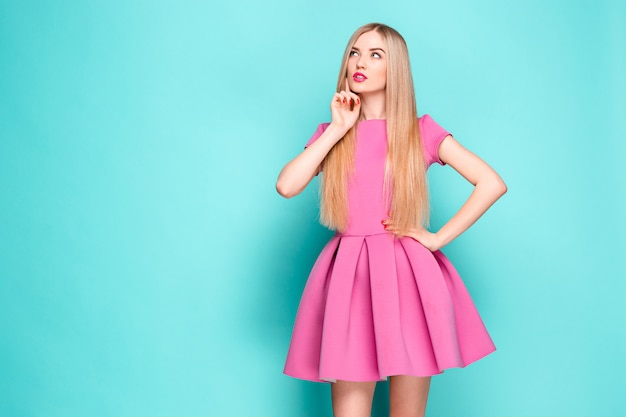 Smiling beautiful young woman in pink mini dress posing, presenting something and looking away Free Photo