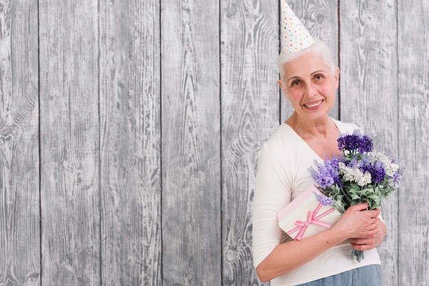 Smiling birthday woman holding purple flower bouquet and gift box in front of gray wooden background Free Photo