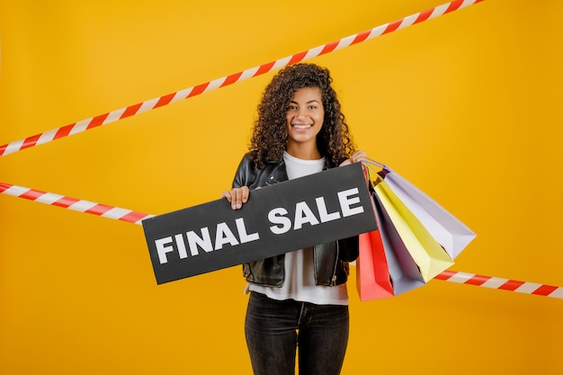 Smiling black girl with final sale sign and colorful shopping bags isolated over yellow with signal tape Premium Photo