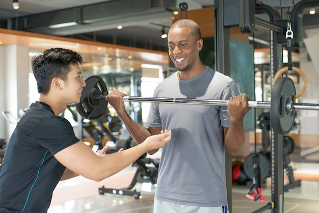 Smiling black man lifting barbell with personal trainer Free Photo
