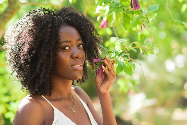 Smiling black woman smelling flowers in park Free Photo