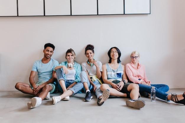 Sorridente giovane nero in camicia blu seduto sul pavimento accanto ai suoi amici. ritratto di interni di studenti internazionali in attesa di esami sul campo. Foto Gratuite