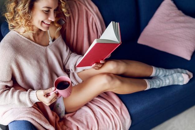 笑顔の金髪の美しい女性が自宅のソファでリラックス。ピンクのニットセーター、暖かい靴下。本を読んで、一杯のコーヒーを保持しています。 無料写真
