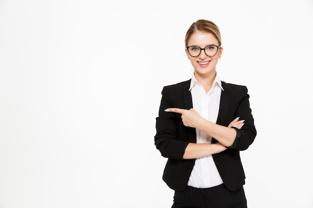 Smiling blonde business woman in eyeglasses pointing away Free Photo