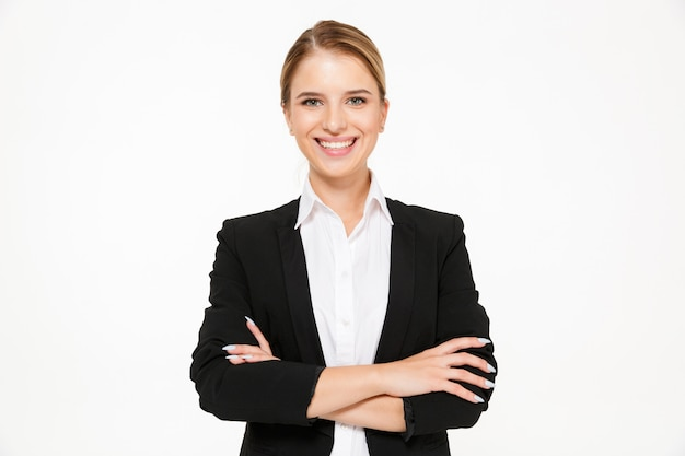 Smiling blonde business woman posing with crossed arms Free Photo