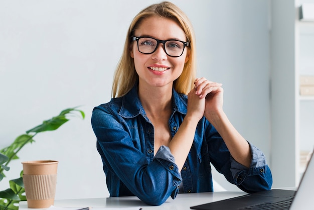 Smiling blonde employee with glasses looking at camera Free Photo