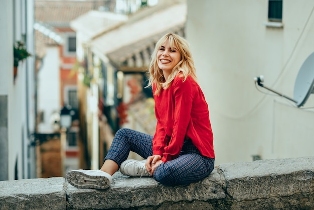 Smiling blonde girl with red shirt enjoying life outdoors. Premium Photo