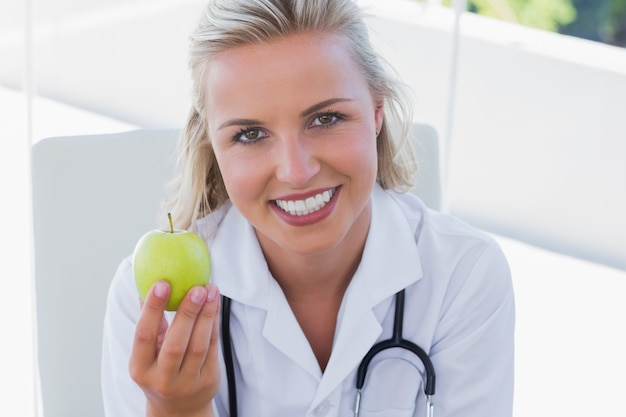 smiling blonde nurse holding a green apple in her office photo