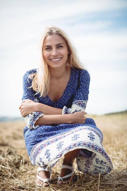 フィールドで身をかがめる笑顔の金髪女性 無料写真