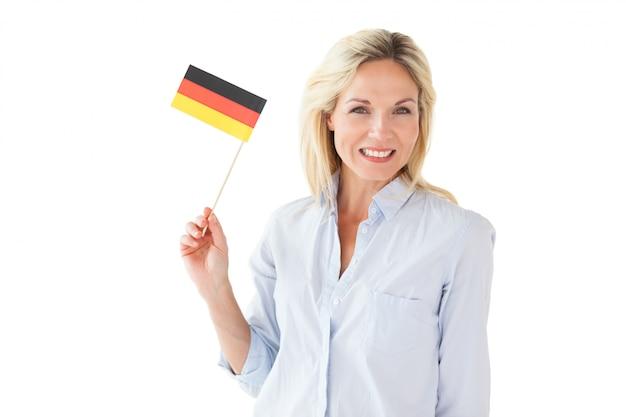 Smiling blonde woman holding german flag Premium Photo
