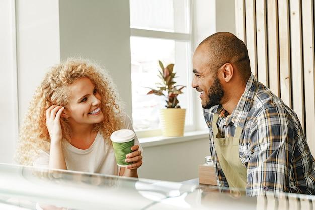 カウンターテーブルでコーヒーショップのウェイターと話している笑顔のブロンドの女性 Premium写真
