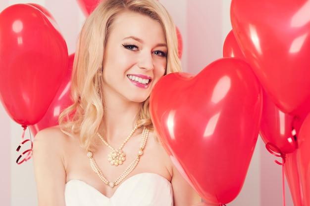 Donna bionda sorridente con palloncini rossi a forma di cuore Foto Gratuite