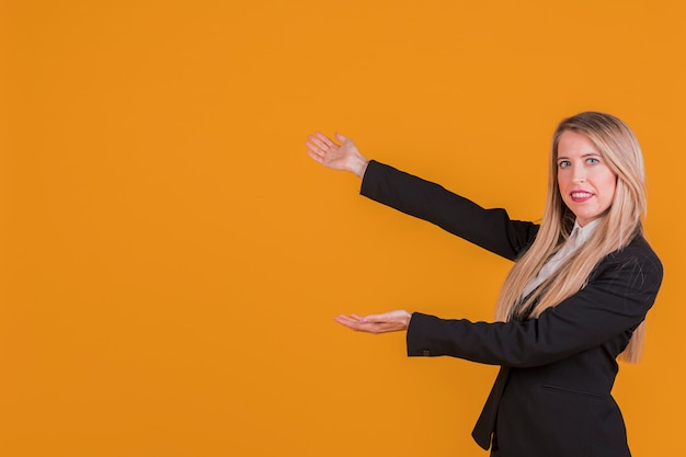 Smiling blonde young businesswoman presenting against an orange backdrop Free Photo