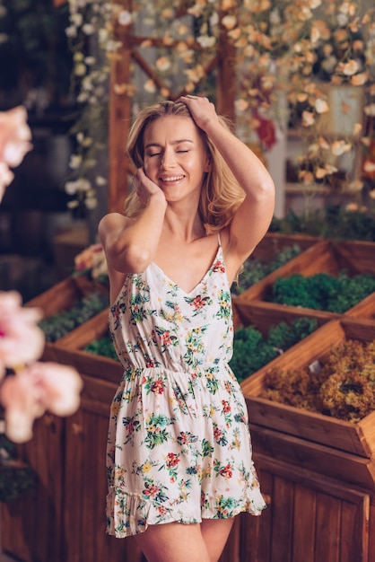 Smiling blonde young woman in floral dress posing at florist shop Free Photo