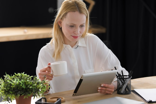 Smiling blonde young woman holding cup of coffee looking at digital tablet Free Photo