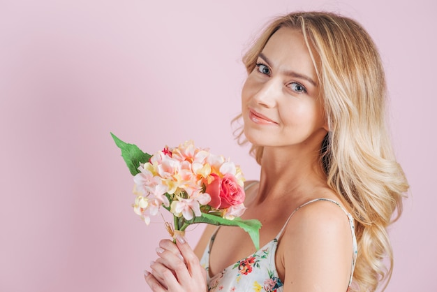 Smiling blonde young woman holding flower bouquet against pink backdrop Free Photo