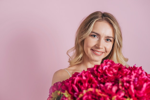 Smiling blonde young woman holding flower bouquet Free Photo