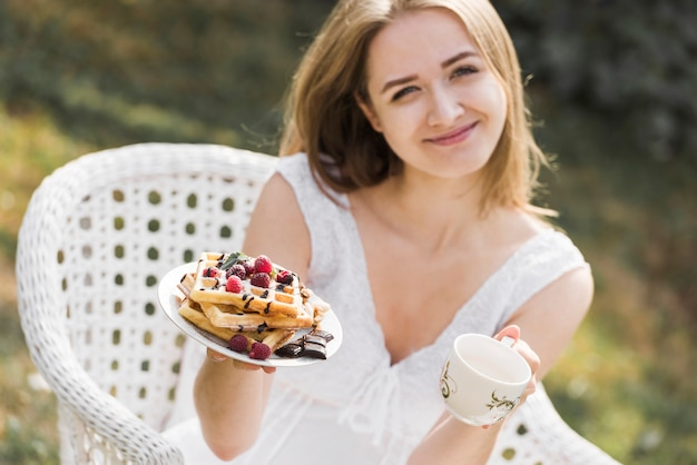 Smiling blonde young woman showing plate of waffles and coffee cup Free Photo
