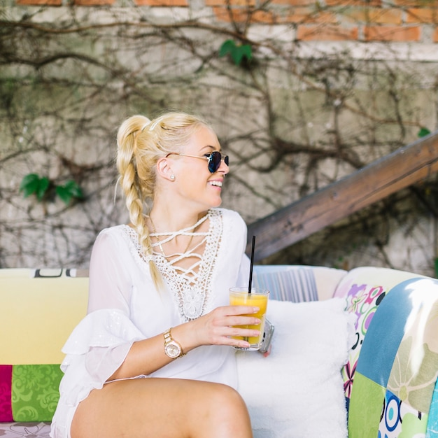 Smiling blonde young woman sitting on sofa holding glass of juice looking away Free Photo