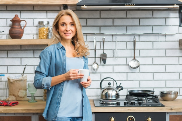 Smiling blonde young woman standing near the gas stove holding white coffee cup Free Photo