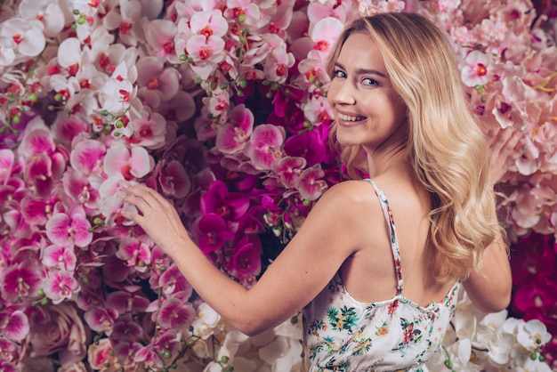 Smiling blonde young woman touching the orchid flowers looking at camera Free Photo