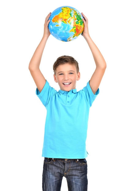 Smiling boy in casual holding globe in hands above his head isolated on white Free Photo