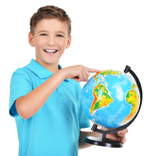 Smiling boy in casual holding globe with in hands and points on it isolated on white Free Photo