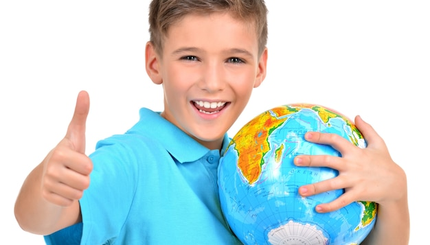Smiling boy in casual  holding globe with thumbs up sign -  isolated on white Free Photo