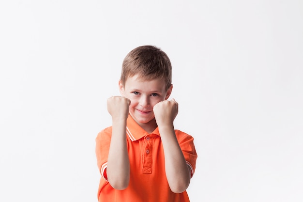 Smiling boy clenching fist making yes gesture on white wall looking at camera Free Photo