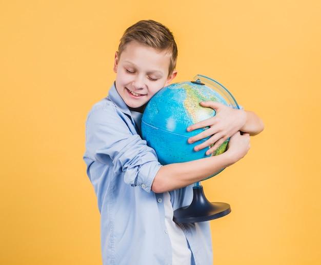 Smiling boy embracing globe hand against yellow backdrop Free Photo