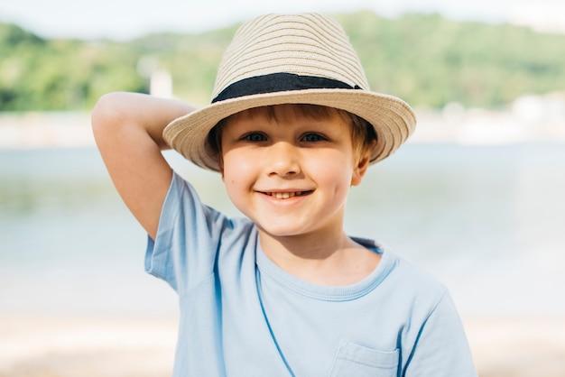 Smiling boy in hat enjoying sunlight Free Photo