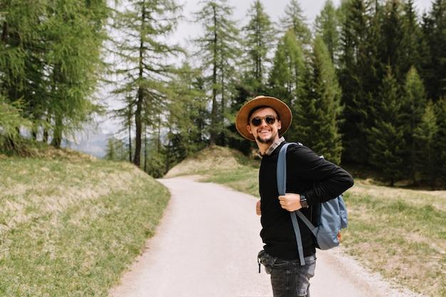休暇で旅行を楽しんで森の道でポーズをとって黒いシャツと帽子の笑顔の少年 無料写真