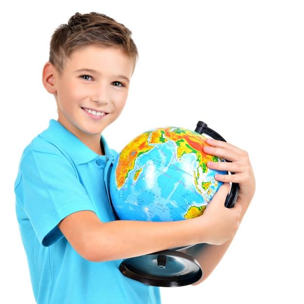 Улыбающийся мальчик в случайном, держа в руках глобус, изолированные на белом Бесплатные Фотографии