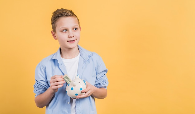 Smiling boy inserting the currency note in the ceramic white piggybank Free Photo