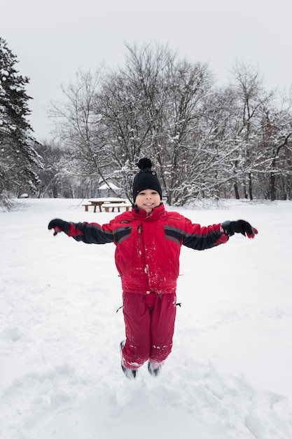 Smiling boy jumping on snowy land in winter season Free Photo