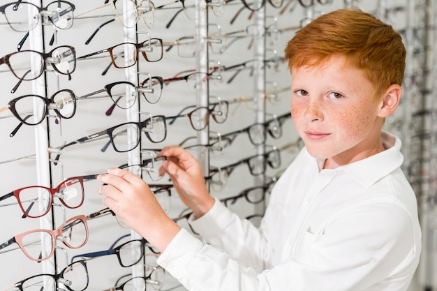 Smiling boy looking at camera while removing eyeglasses front display rack Free Photo