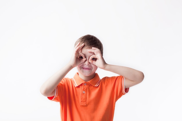 Smiling boy looking through ok hand gesture on white backdrop Free Photo