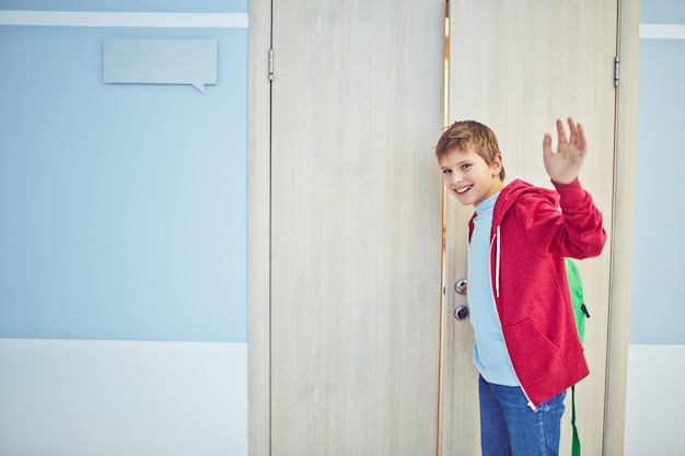 Smiling boy saying goodbye Free Photo